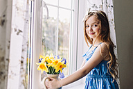 Portrait of smiling girl with flower vase of daffodils and hyacinths at home - NMSF00043