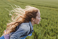 Girl with blowing hair running on a field - NMSF00049