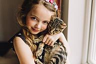 Portrait of little girl holding tabby kitten - NMSF00052