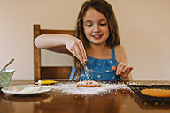 Girl decorating biscuits at home - NMSF00055