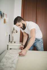 Young man making the bed at home - RAEF01848