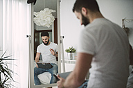 Young man sitting on his bed using a tablet - RAEF01851
