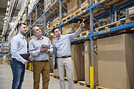 Three men with tablet talking in factory warehouse - DIGF01719
