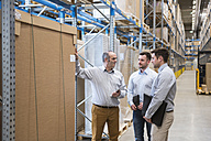 Three men with tablet talking in factory warehouse - DIGF01722