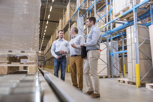 Three men talking in factory warehouse - DIGF01725