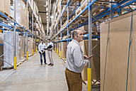 Man with tablet and two men with folder in factory warehouse - DIGF01728