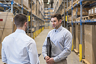 Two men talking in factory warehouse - DIGF01731
