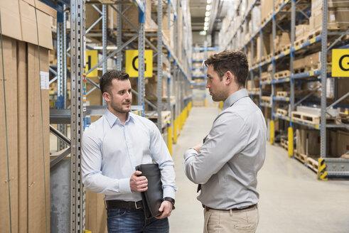Two men talking in factory warehouse - DIGF01734