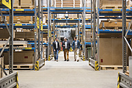 Three men walking in factory warehouse - DIGF01737
