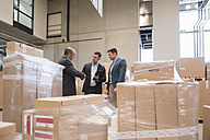 Three men in factory warehouse surrounded by cardboard boxes - DIGF01743
