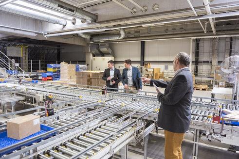 Three businessmen at conveyor belt in factory - DIGF01758