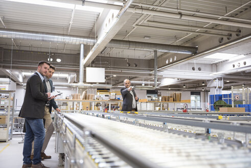 Three businessmen at conveyor belt in factory - DIGF01761