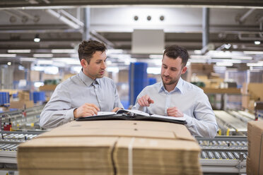 Two men in factory warehouse looking at documents - DIGF01773