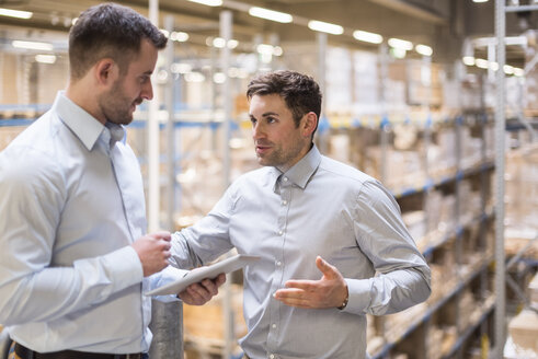 Two men with tablet talking in factory warehouse - DIGF01776