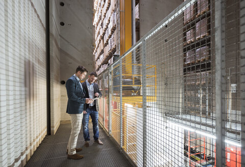 Two men in automatized high rack warehouse looking at tablet - DIGF01782