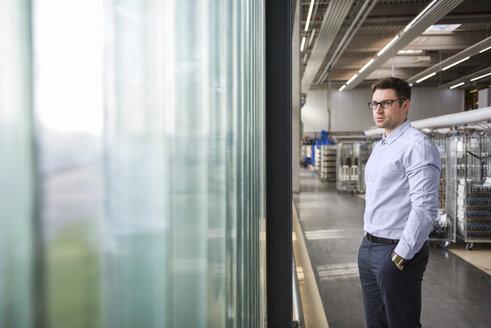 Businessman standing in factory shop floor - DIGF01836