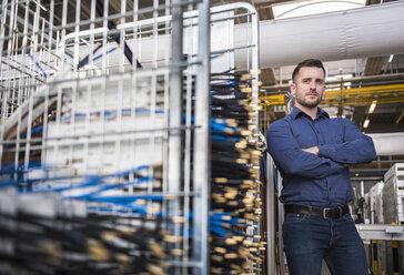 Portrait of confident businessman in factory shop floor - DIGF01839