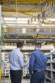 Two men with tablet talking in factory shop floor - DIGF01851