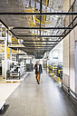 Businessman walking in factory shop floor looking at cell phone - DIGF01854