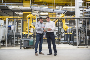 Two men with tablet talking in factory shop floor - DIGF01857