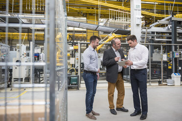 Three men with tablet talking in factory shop floor - DIGF01860