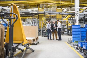 Three men talking in factory shop floor - DIGF01863