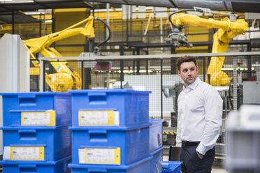 Businessman standing in factory shop floor - DIGF01866