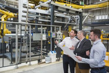 Three men with blueprint talking in factory shop floor - DIGF01869