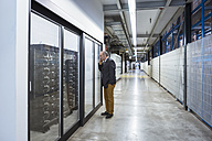 Businessman in factory shop floor talking on the phone - DIGF01881