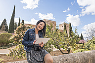 Spain, Granada, happy young woman with tablet at the Alhambra - JASF01730