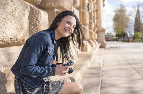 Spain, Granada, happy young woman with camera at the Alhambra - JASF01736