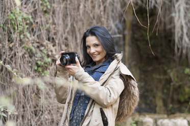 Portrait of smiling young woman with camera outdoors - JASF01739