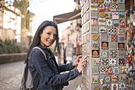 Spain, Granada, smiling young woman at Albayzin district at a souvenir stall - JASF01751