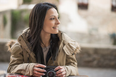 Smiling young woman with camera outdoors - JASF01754