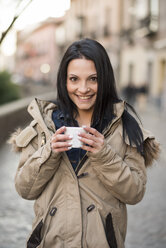 Spain, Granada, smiling young woman holding cup at Albayzin district - JASF01757