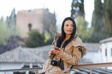 Spain, Granada, young woman with camera and cell phone in front of the Alhambra - JASF01763