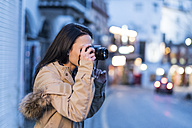 Spain, Granada, young woman taking pictures at Albayzin district at dusk - JASF01766