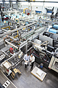 Top view of two men in factory shop floor talking about product - DIGF01895