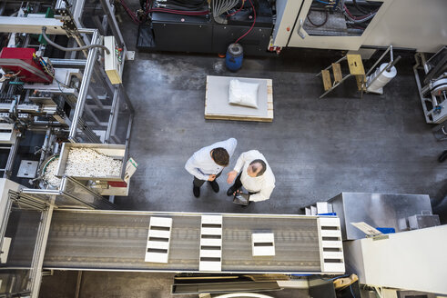 Top view of two men with tablet talking in factory shop floor - DIGF01898