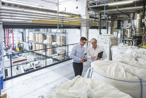 Two men talking about materials in factory - DIGF01916