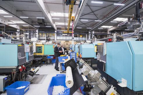 Two men talking in factory shop floor - DIGF01928