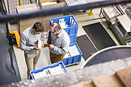 Top view of two men in factory shop floor talking about product - DIGF01961