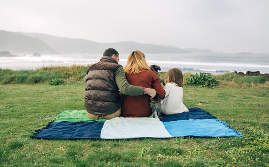 Back view of family with dog sitting on blanket at the coast - DAPF00696