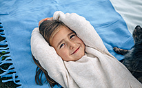Portrait of smiling girl lying on blanket with dog - DAPF00699