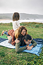 Happy family on blanket at the coast - DAPF00702