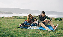Family with dog sitting on blanket at the coast using wireless devices - DAPF00708