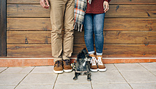 Low section of couple with dog standing in front of wooden wall - DAPF00711