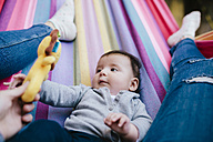 Mother and baby girl lying on a hammock playing together - GEMF01592