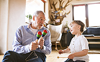Grandfather and grandson playing music at home - HAPF01504