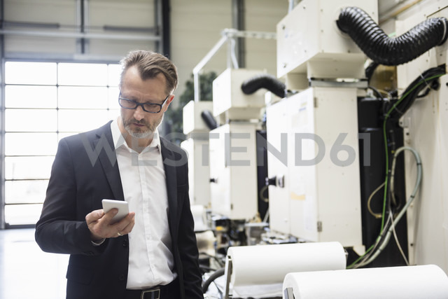Businessman in factory shop floor looking on the phone - DIGF02020